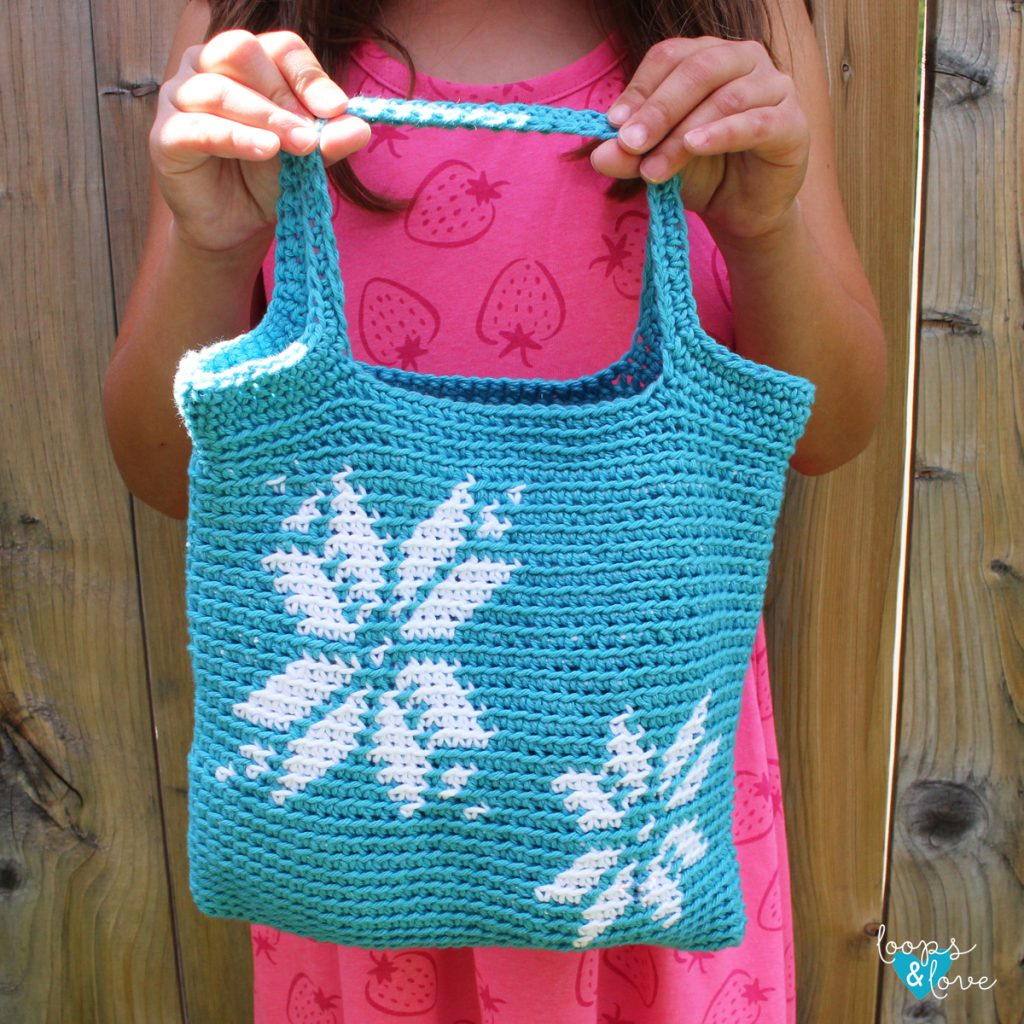 hands holding a crochet bag with snowflakes Christmas in July