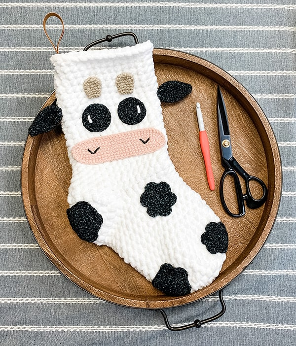 a cow themed stocking displayed on a platter Christmas in July
