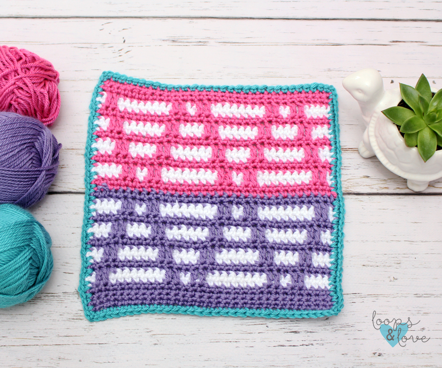A crocheted mosaic triangles square beside yarn and a succulent